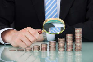 Midsection of young businessman examining coins stacked as bar graph at office table